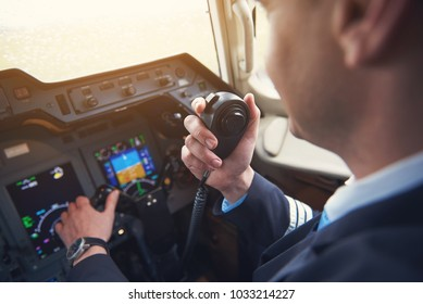 Close up pilot hand taking by portable radio set in cabin while navigating plane. Occupation and communication concept