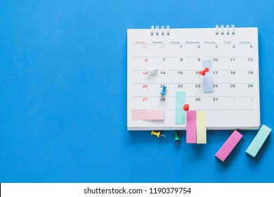 close up of pin on calendar on the blue table background, planning for business meeting or travel planning concept