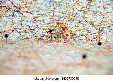 close up of pin sticks into a real map. travelling to berlin. pin marking location on map. maps navigation with red and black color point markers, design background. Travel concept with push pins.