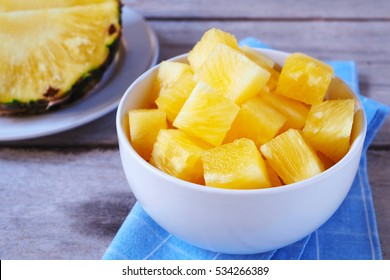 Close up of pineapple cube in a bowl on a wooden table.