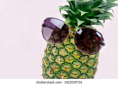 Close up of pineapple with sunglasses on violet background