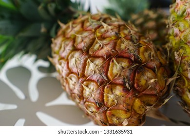 Close up of a pineapple in a white flower-shaped metal bowl.
