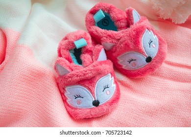 Close up of pink baby shoes on a wood background. Greeting card