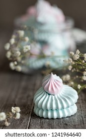 Close up of pink and blue meringues on dark backgrouns