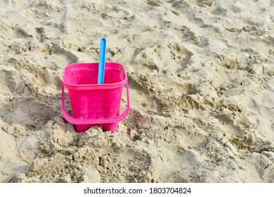 close up of pink plastic sand castle bucket with blue spade on sand  beach in summer sunshine