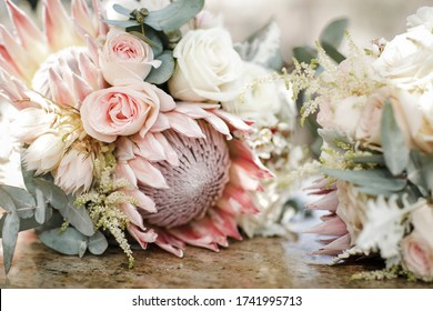 Close up of pink roses on wedding bouquet with protea, white roses and eucalyptus leaves