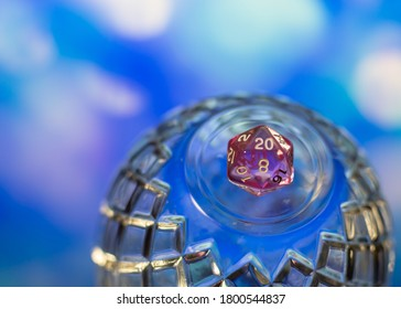 Close up of a pink transparent d20 polyhedral dice on top of a crystal dome against a blurry background.