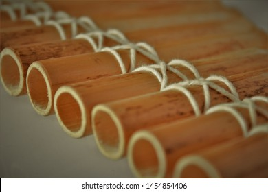 Close up of a pipe flute made from pieces of bamboo and tied together with string, against a plain background