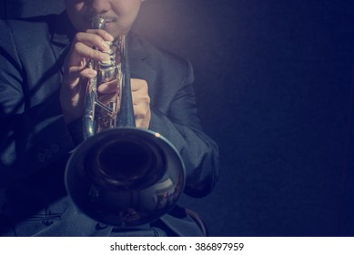 Close up Pipes in the hands of trumpet player on dark,low key and retro image