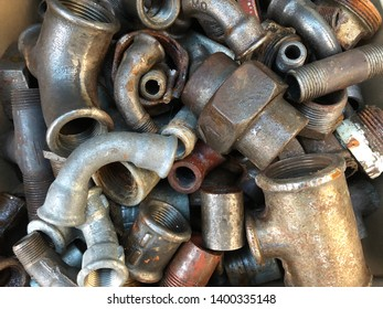 Close up of pipes and plumbing parts in a container at a scrap yard.