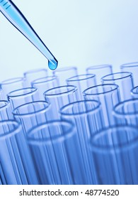 Close up of a pipette dropping a blue sample into a test tube.