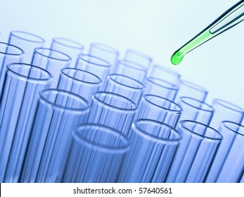 Close up of a pipette dropping a green sample into a test tube.