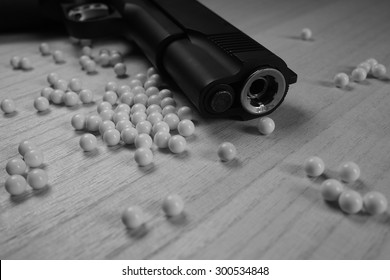 Close up of pistol. 11 mm or 0.45 and BB gun bullet. Black and White. Shallow depth of field.