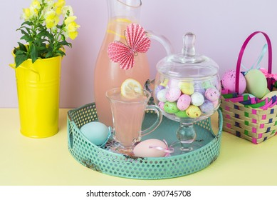 Close up of pitcher, decorated  paper butterfly, and glass with pink lemonade.  jar with chocolate candy eggs in a metal tray.
