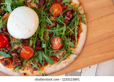 Close up of a pizza on a wooden board with cherry tomatoes, arugula, and burrata cheese on a wooden table