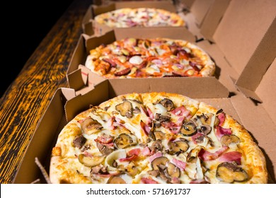 Close up of pizzas with variety of toppings and cheese in cardboard take out boxes with open lid on wooden table