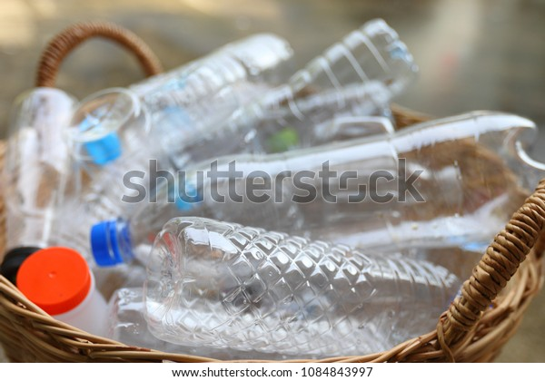 Close up plastic garbage bottles in brown bamboo basket recycle concept, bokeh background