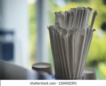 Close Up plastic straws with paper wrappers in cup container in restaurant on blur background.
