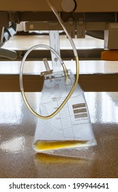 Close up plastic urine collection bag hang under patient bed in hospital