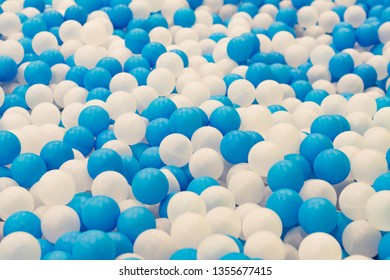 Close up of plastic white and blue balls in dry pool on the playground