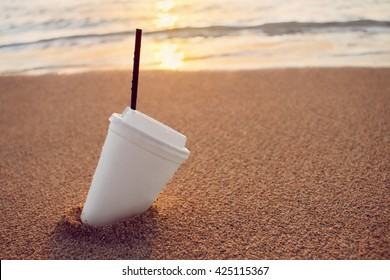 Close up plastic white coffee cup with black straw on sand of beach at sunset or sunrise sunlight on background, toned, selective focus