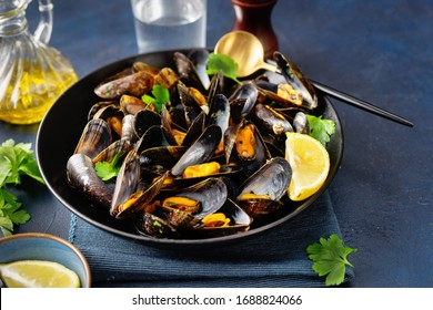 Close up of a plate with freshly coocked mussels on dining table