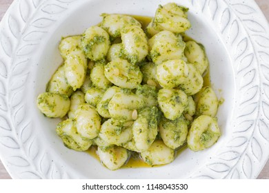 Close up of a plate of green gnocchi.