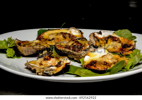 A close up of a plate of grilled oysters with Creole garlic butter and cheese