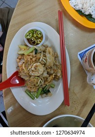 close up of a plate of local Malaysian hawker street food delicacy sar hor fun which is a flatted rice noodle cake fried with prawns or shrimp and vegetable