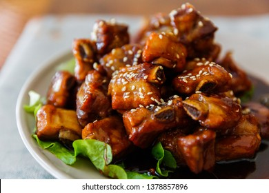 Close up of a plate of sweet and sour pork ribs with white sesame seeds under natural light