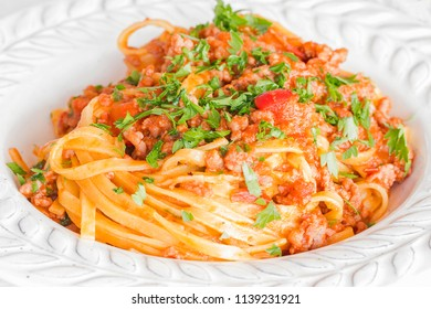 Close up of a plate of Tagliatelle with ragu sauce.