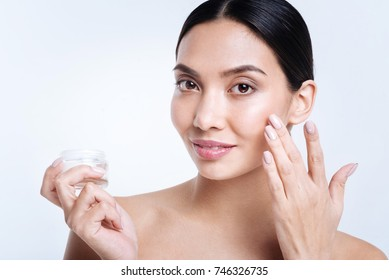 Close up of pleasant woman applying cream to her face