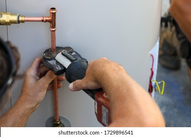A close up of a plumber installing an electrical hot water cylinder.