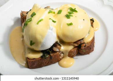 Close up of poacheg eggs with bacon, shpinach and hollandaise sause