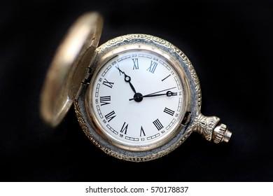 Close up pocket watch on black background