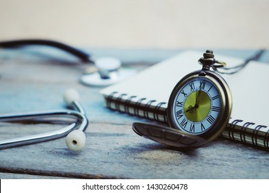 close up pocket watch, stethoscope and notebook on old wood table, saving and manage time for healthy, world health day, medical and healthcare business technology concept, vintage tone