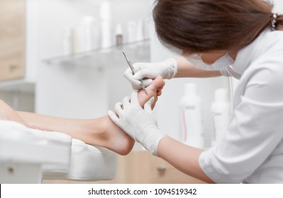 Close up of podiatrist doctor making cleaning procedure for client foot with special long iron tool. Relax at beauty salon, caring about legs. Podiatry and pedicure concept.