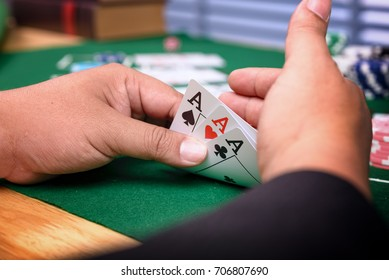 Close up poker hands with cards and chips on green casino table. Concept about entertainment and gambling.