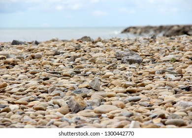 close up of polished little stones on a beach in south of France, with the mediterranean sea and the sky in background