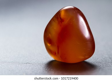close up of a polished piece of carnelian isolated on a black background