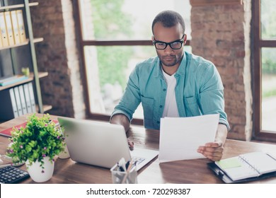 Close up of ponder young afro american emigrant economist with bristle sitting at his work place, looking at the doc, typing data in device, modern interior, nice workstation, trendy eyewear