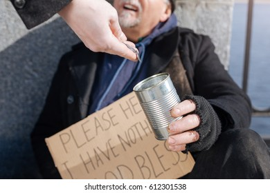 Close up of poor man holding tin for coins