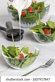 Close up of poppyseed dressing being poured into a spinach and tomato salad with other bowls of the salad in behind.