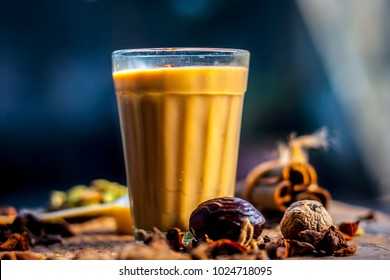 "Close up of popular Indian/Asian drink ""  Masala Chai"" or Spicy tea/normal tea with all the ingredients including sugar on a wooden surface."