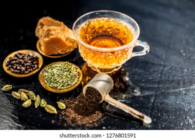 Close up of popular type of tea on wooden surface earlier dunked a lot i.e. Jaggery tea with ingredients like fennel,jaggery or gud,black pepper,tea leaves, milk, and green cardamom.