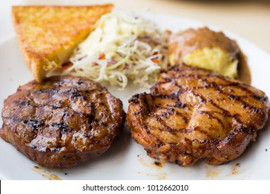 Close up pork and chicken spicy steak grill on white dish and there are bread and mash potato that is side dish for lunch or dinner and for concept design or web design or business