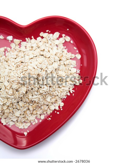 Close up of porridge oats on a heart shaped plate - isolated against white