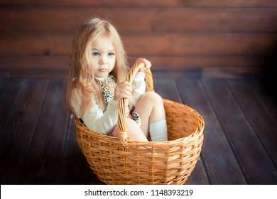 Close up portait of pretty cute infant girl showing different emotions sitting in basket at home on wooden background. Happiness, childhood, posotive concept