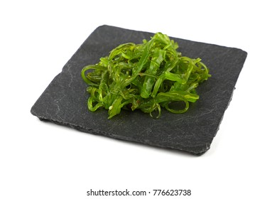 Close up portion of green wakame seaweed salad on square black slate board plate isolated on white background, high angle view