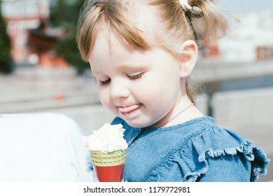 Close up portrait of a 3 years old girl eating ice cream in a city park on a warm sunny day